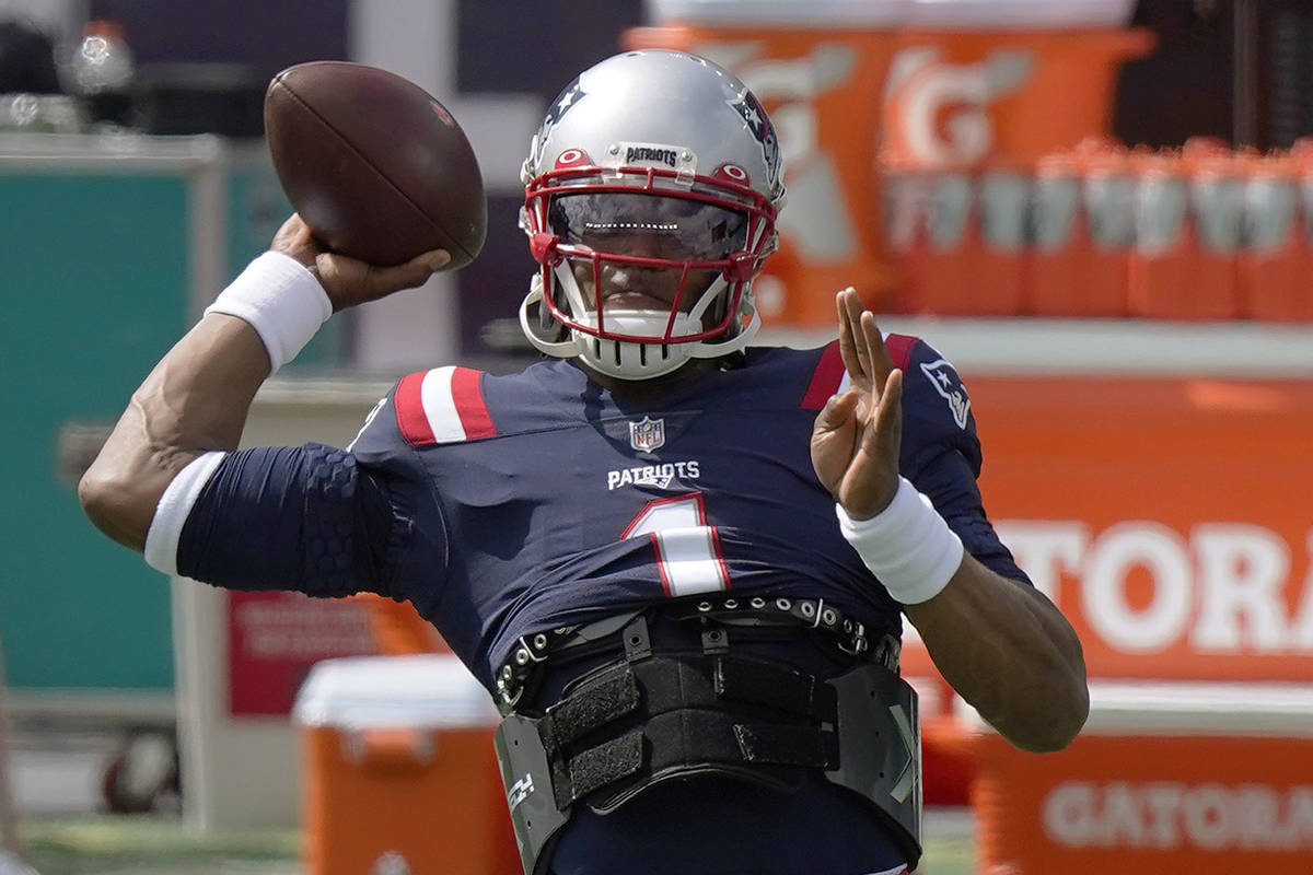 New England Patriots quarterback Cam Newton warms up before an NFL football game against the Mi ...