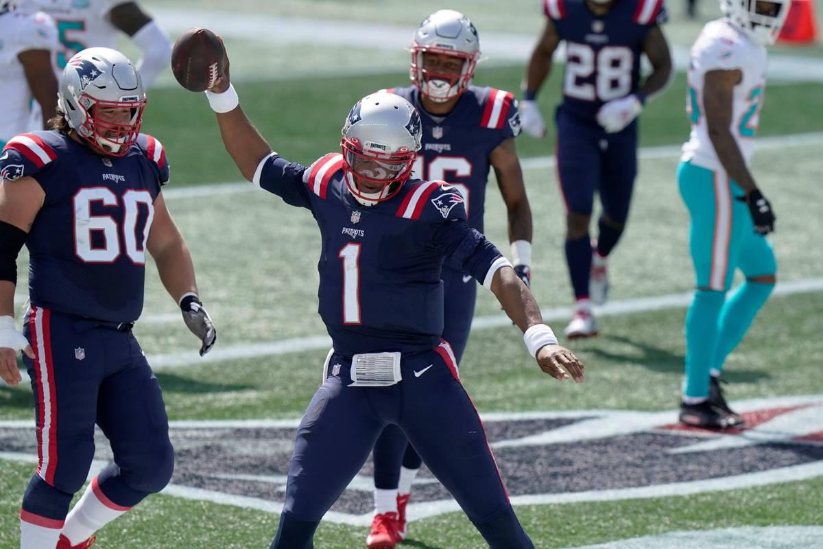 New England Patriots quarterback Cam Newton (1) celebrates his rushing touchdown against the Mi ...