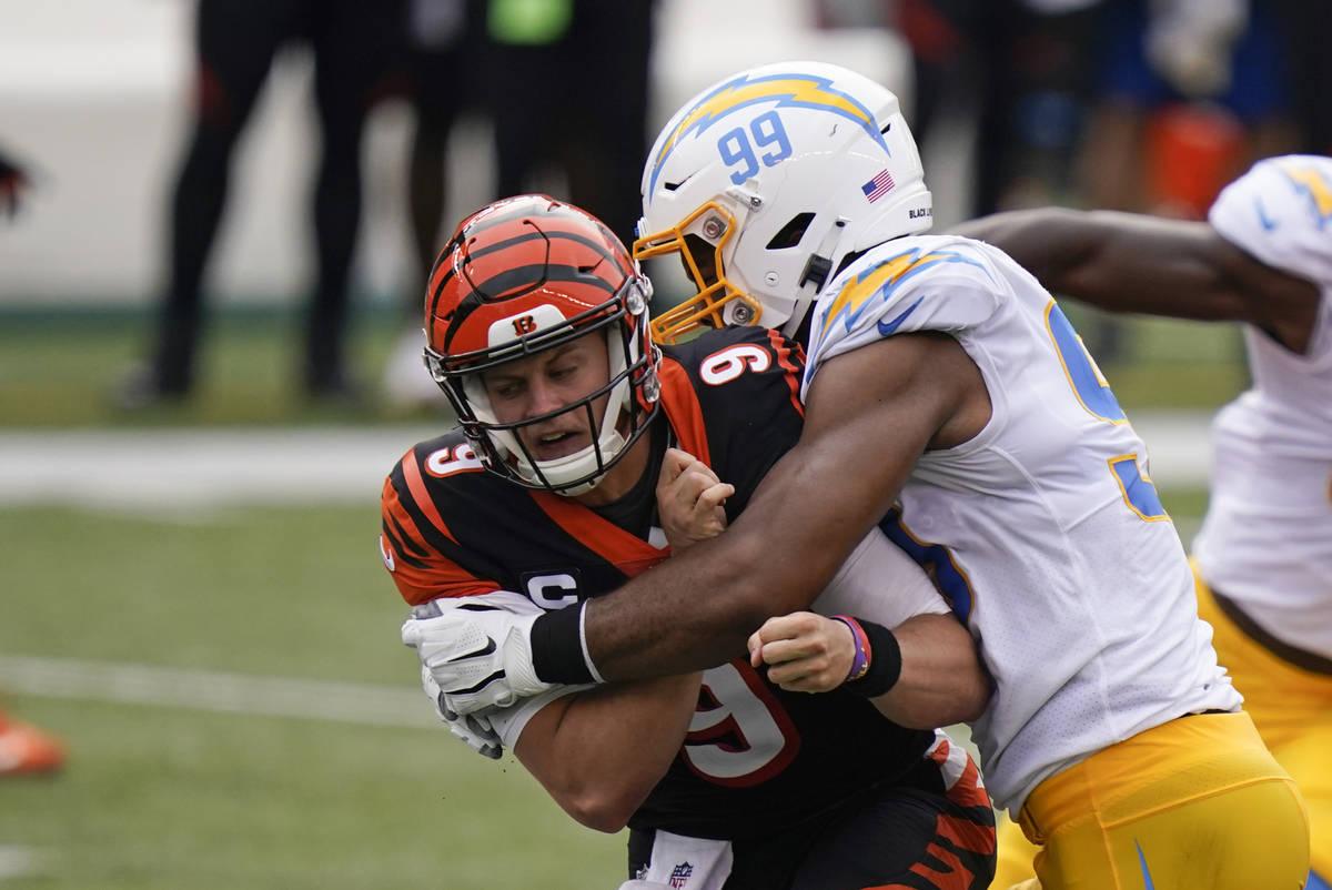 Cincinnati Bengals quarterback Joe Burrow (9) is hit by Los Angeles Chargers' Jerry Tillery (99 ...
