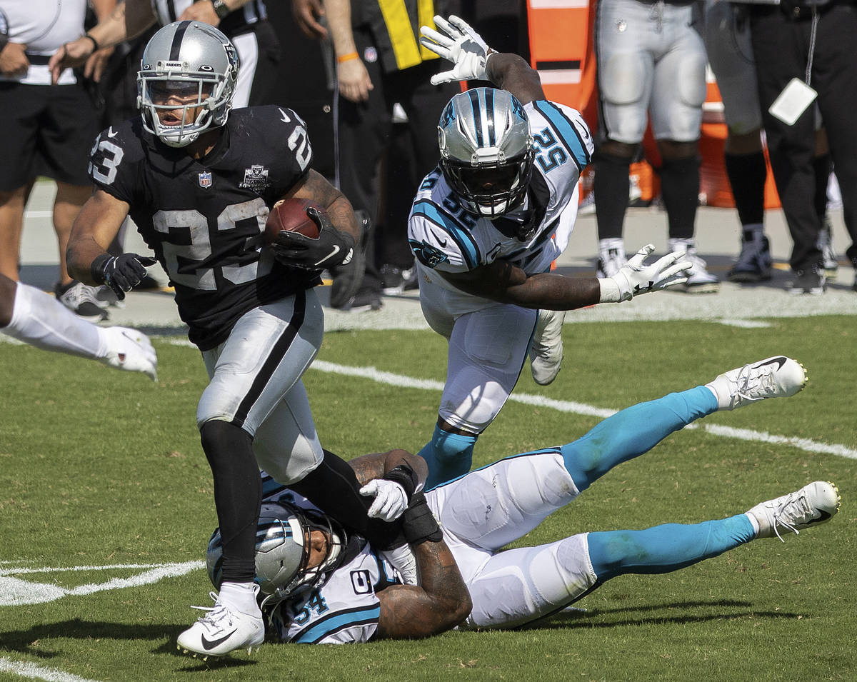 Las Vegas Raiders running back Devontae Booker fights for extra yardage with Carolina Panthers ...