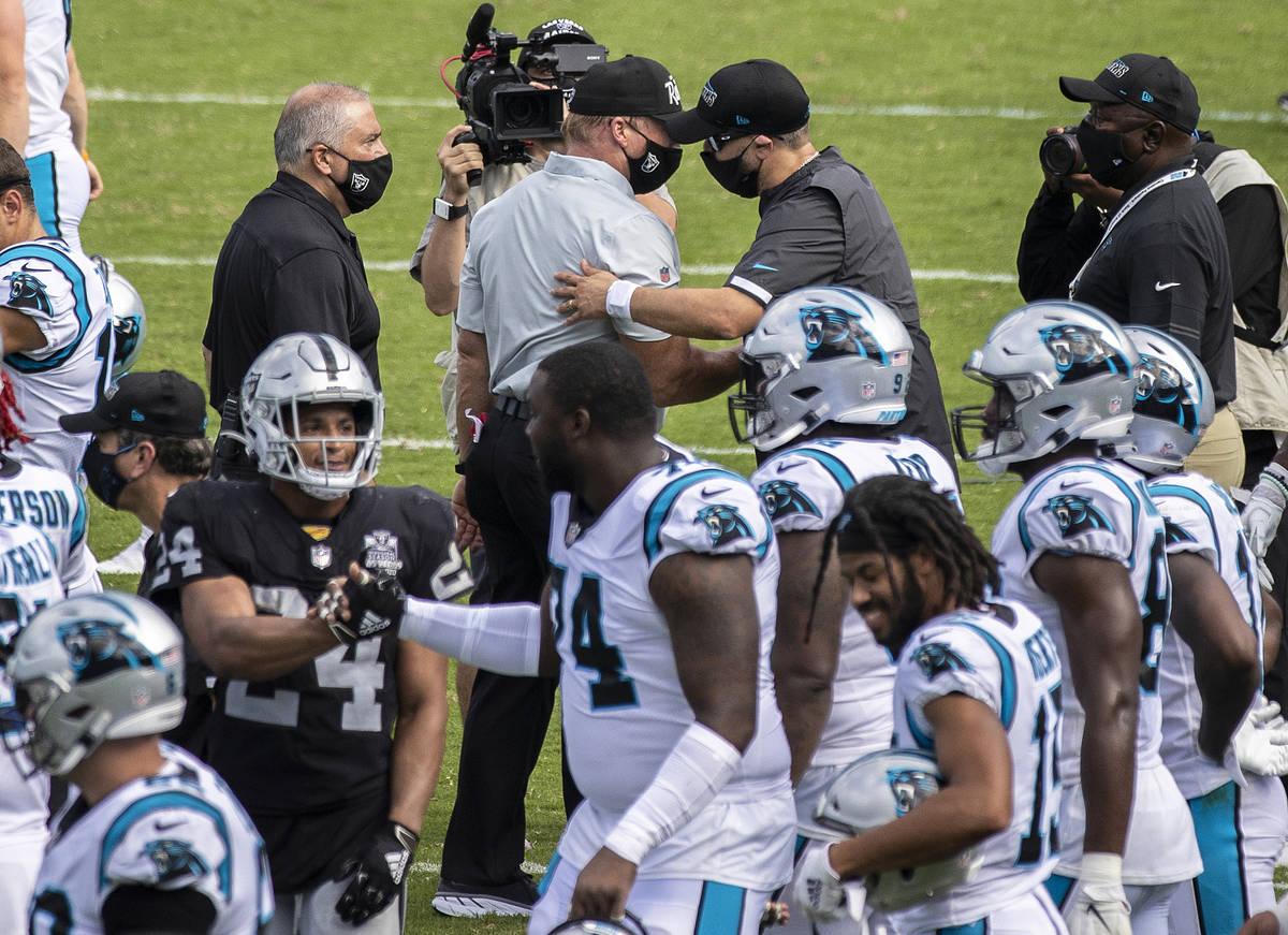 Las Vegas Raiders head coach John Gruden, top/left, shakes hands with Carolina Panthers head co ...