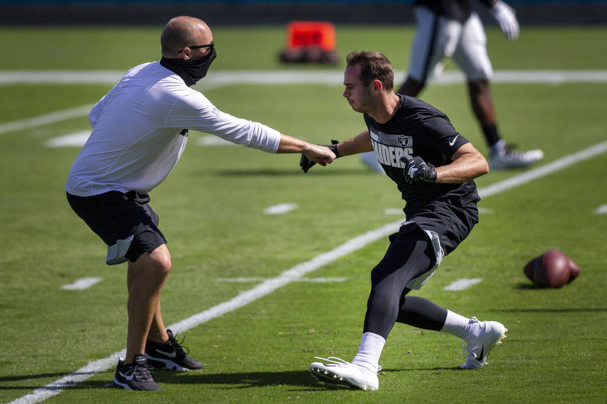 Las Vegas Raiders wide receiver Hunter Renfrow, right, works with offensive quality control coa ...