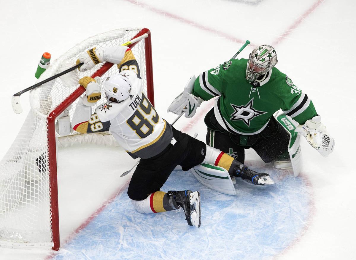Dallas Stars goalie Anton Khudobin (35) watches as Vegas Golden Knights' Alex Tuch (89) crashes ...