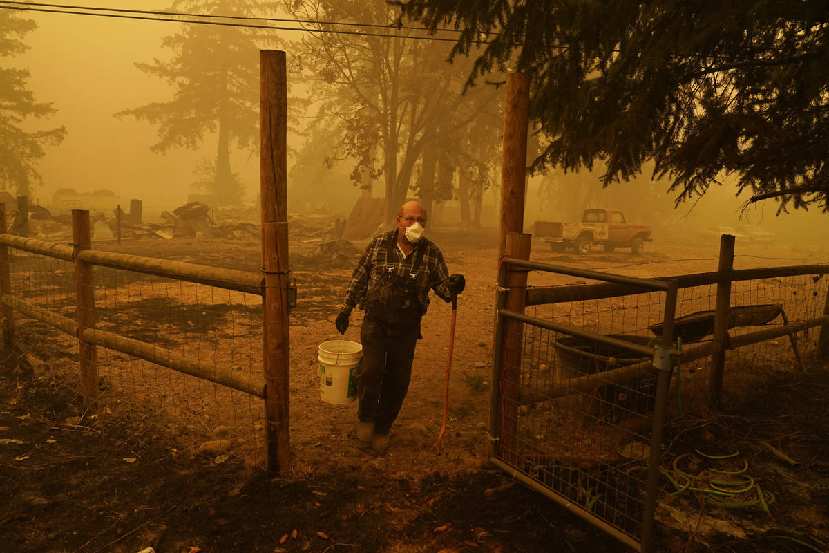 George Coble carries a bucket of water to put out a tree still smoldering on his property destr ...