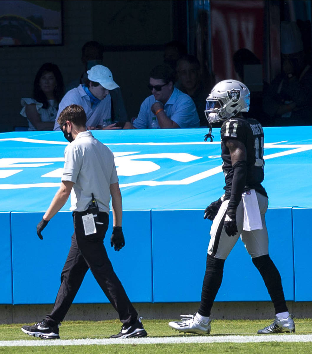 Las Vegas Raiders wide receiver Henry Ruggs III (11) walks off the field with a trainer in the ...