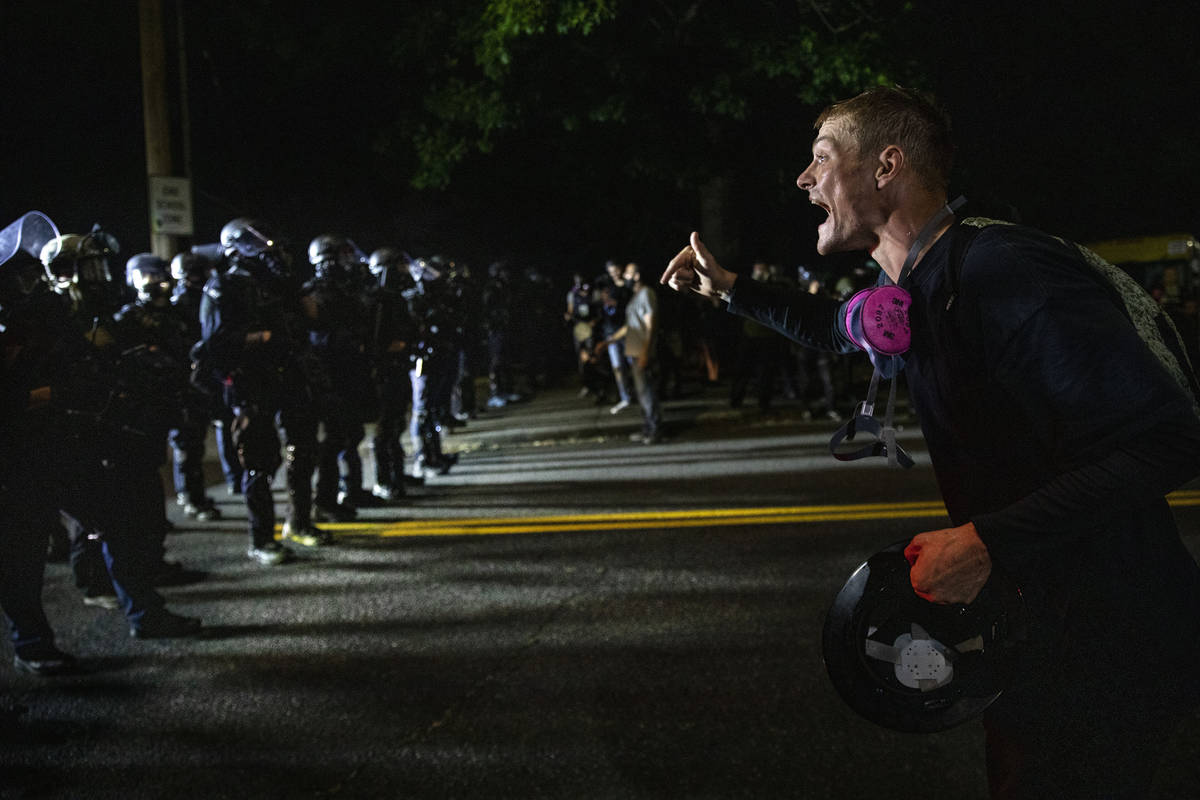 A protester screams at police as as Portland protests continue reaching 100 consecutive nights ...