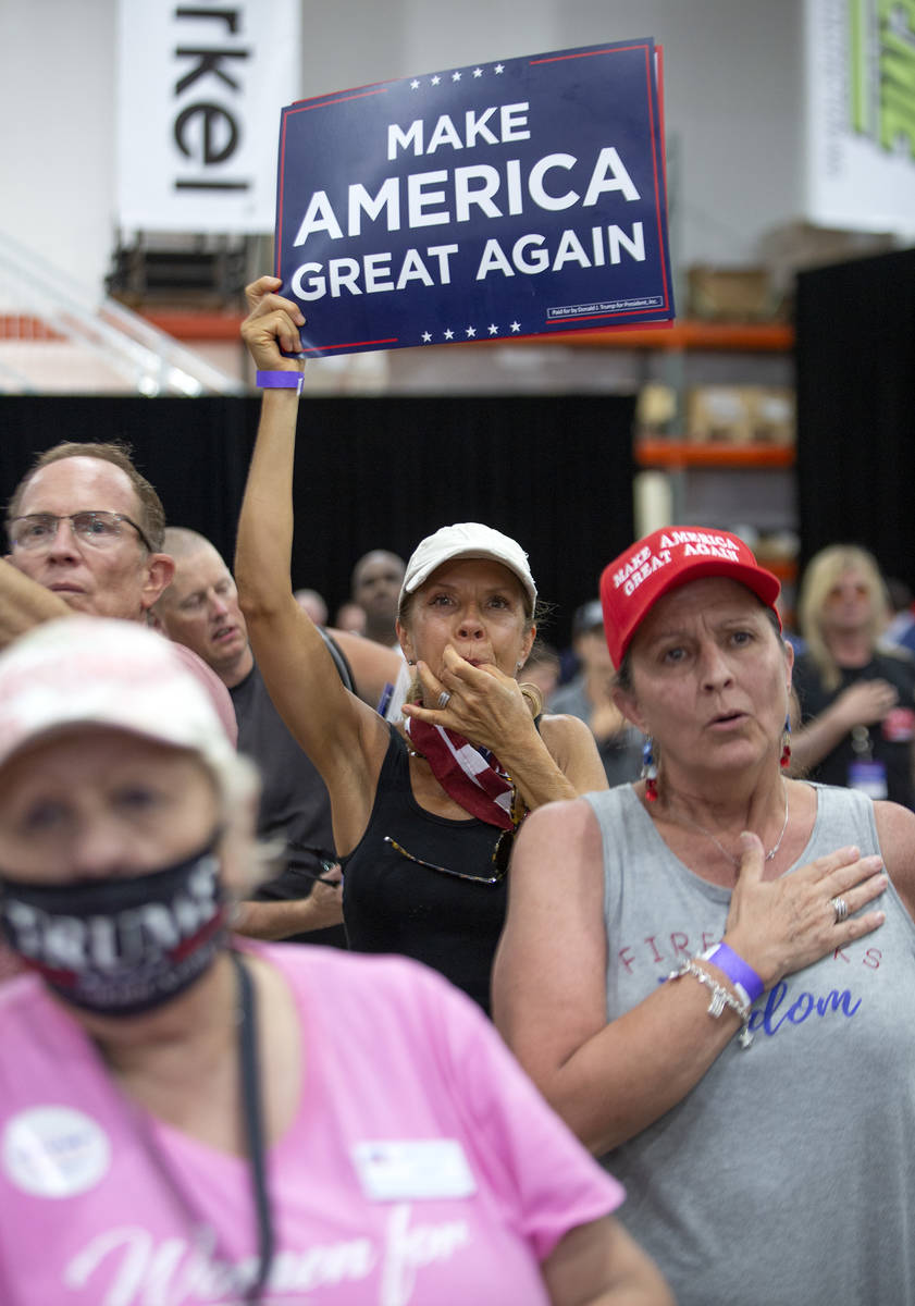 Attendees of a Trump campaign rally participate in the national anthem at Xtreme Manufacturing ...