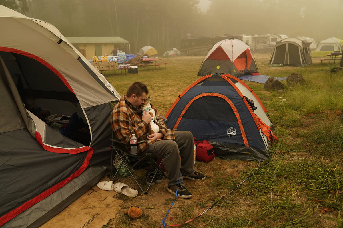 Kristopher Smith holds his dog Tripp outside his tent at an evacuation center at the Milwaukie- ...