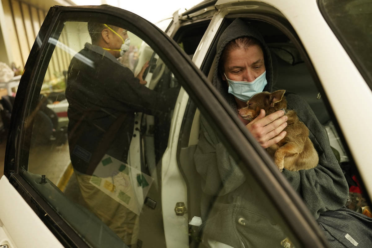 Beth Deleo holds her dog as Ben Quaempts loads donated items into their van at the Milwaukie-Po ...