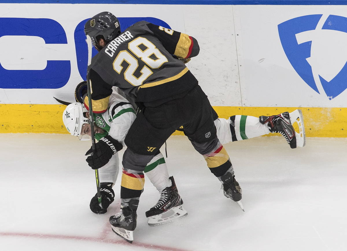 Dallas Stars' Jason Dickinson (18) is checked by Vegas Golden Knights' William Carrier (28) dur ...