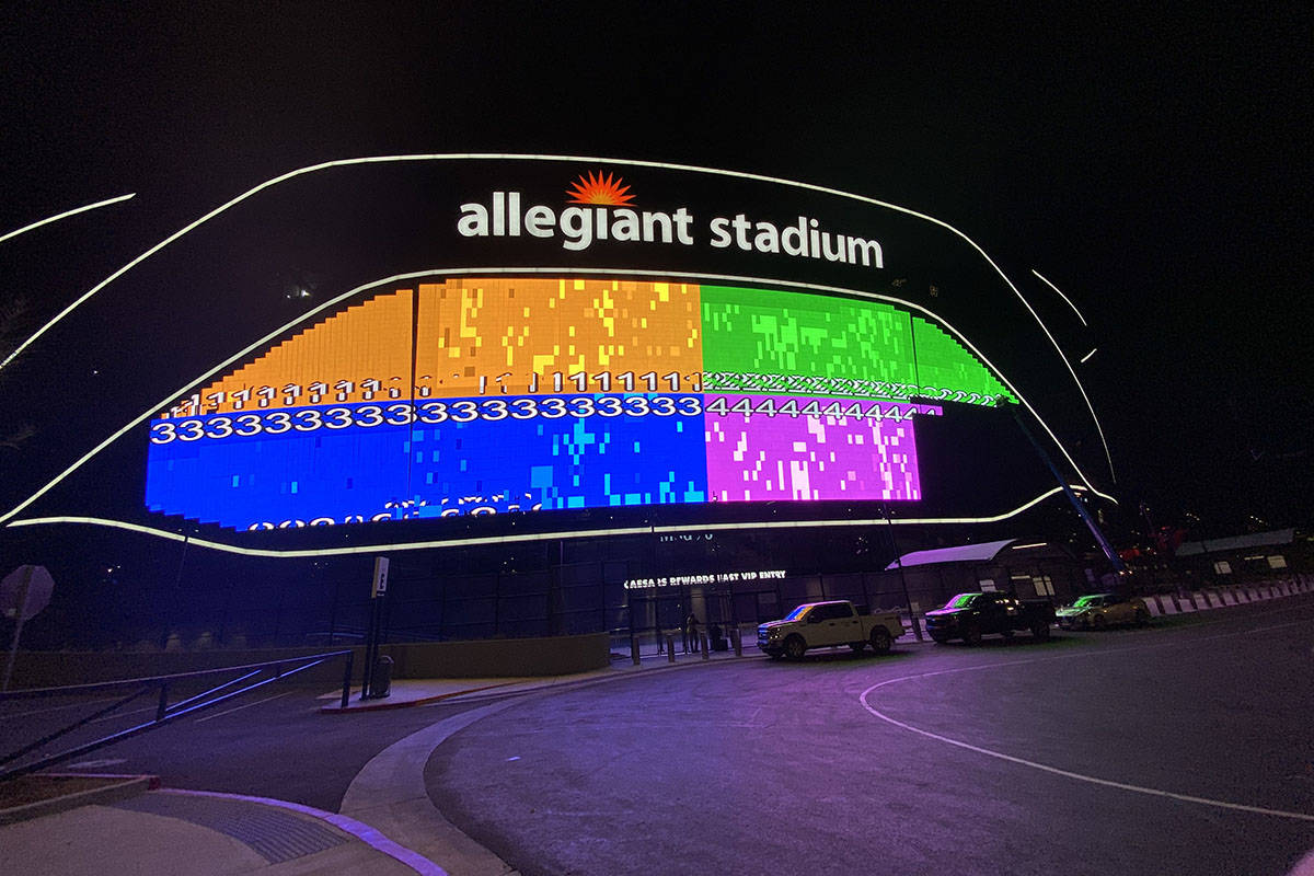 The massive video board lit up on the Interstate 15 facing portion of Allegiant Stadium. (Mick ...