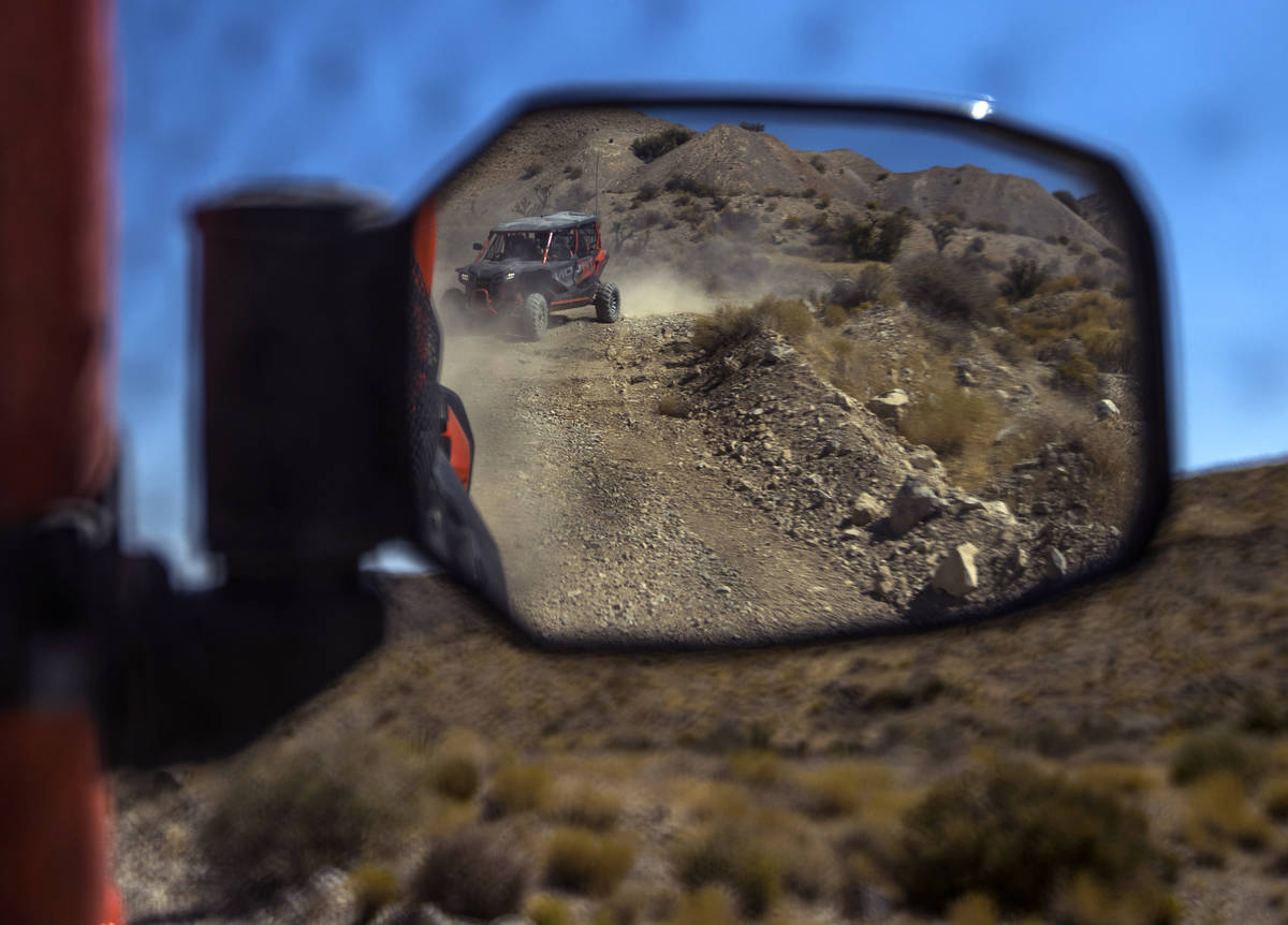 A Honda Talon is reflected in the mirror of another as the vehicles move along the miles of dir ...