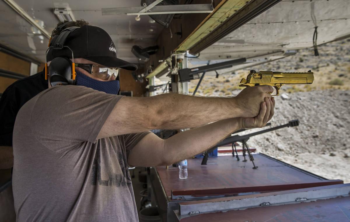 Christopher Lawrence aims a titanium gold Desert Eagle pistol on the Adrenaline Mountain gun ra ...