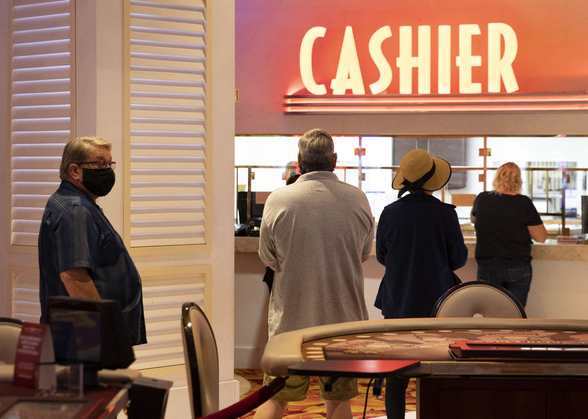 Gusts lined up at cashier booth after the Tropicana hotel-casino reopens to public, on Thursday ...