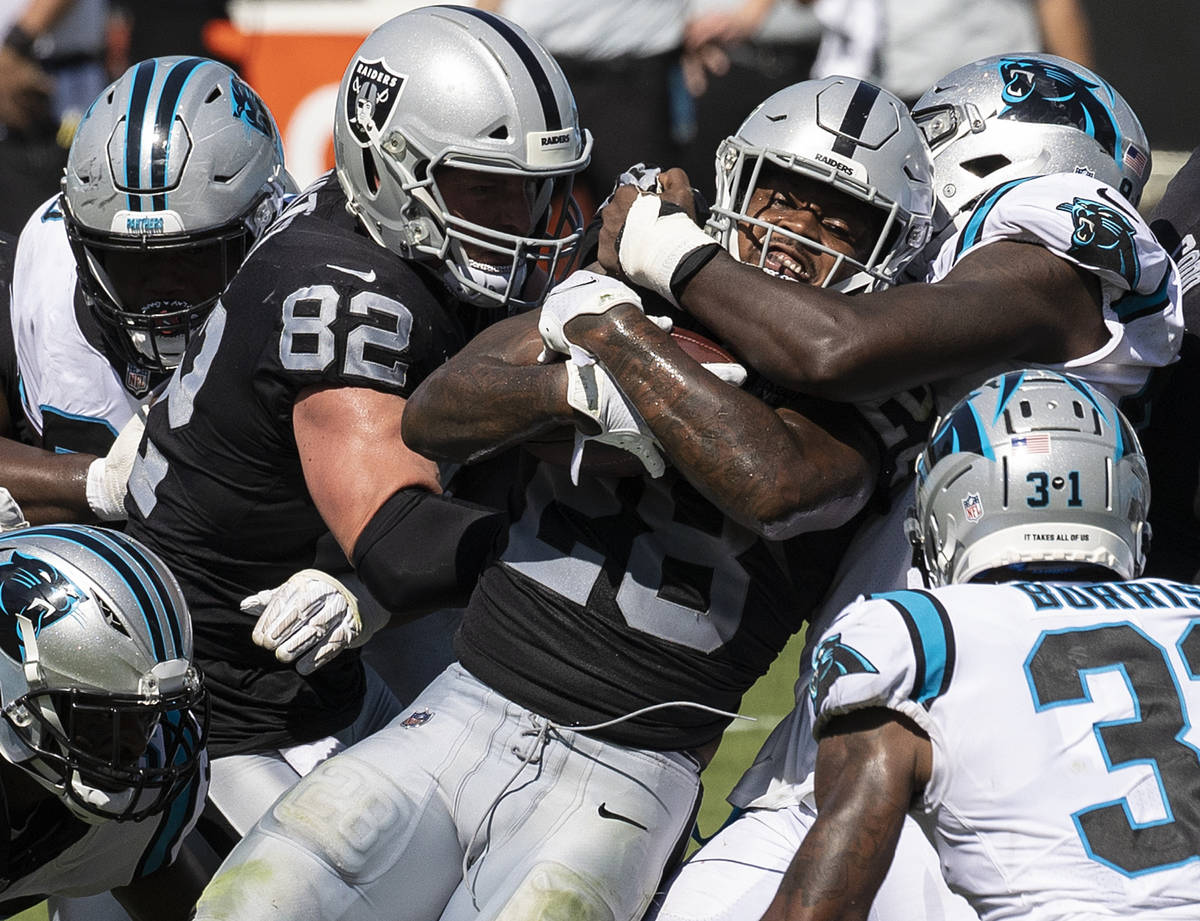 Las Vegas Raiders running back Josh Jacobs (28) is stacked up by Carolina Panther defenders in ...