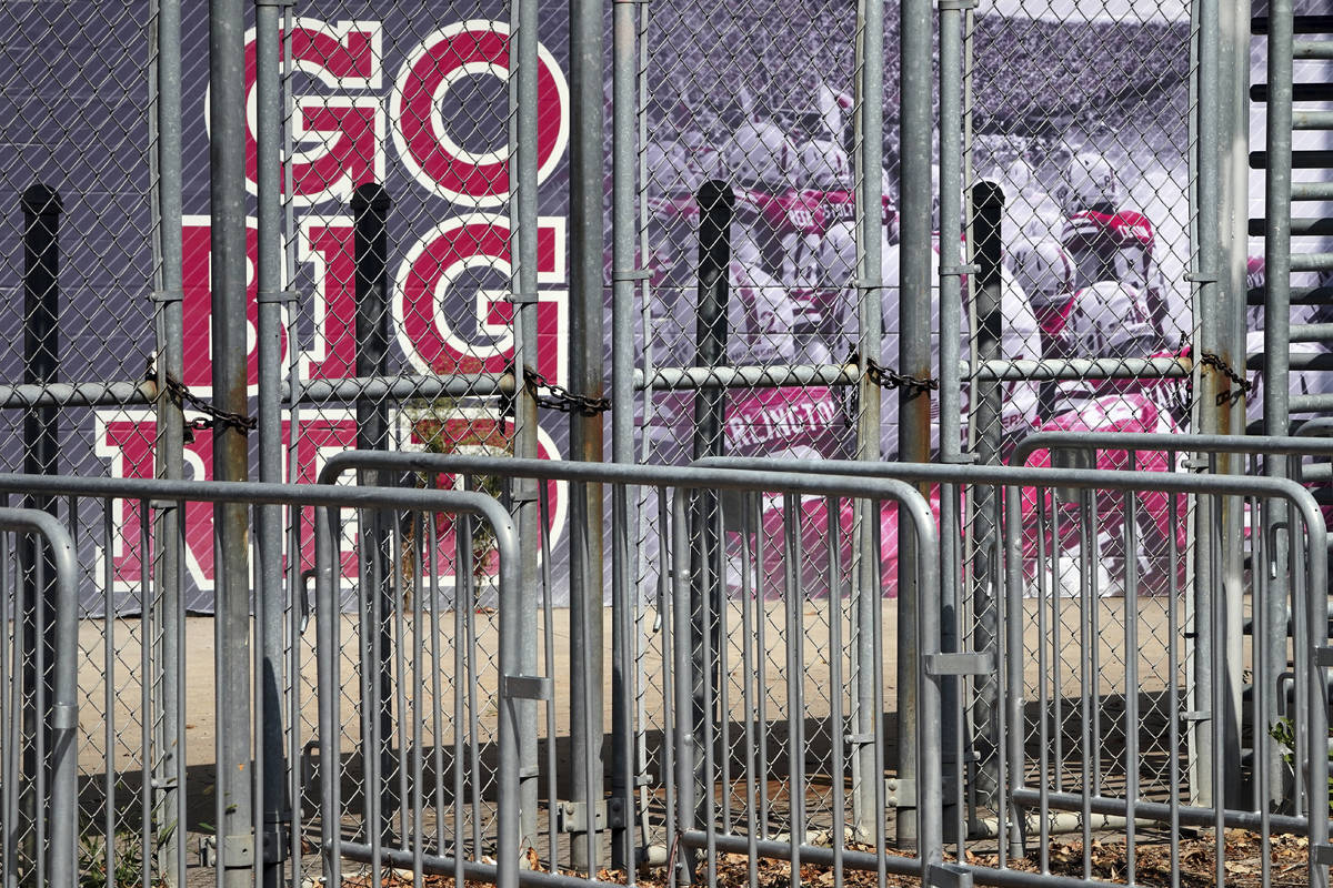 A mural showing Nebraska football players and Go Big Red lettering are seen past locked gates a ...