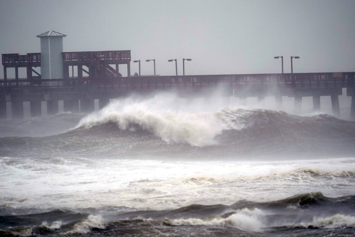 Waves crash near a pier, at Gulf State Park, Tuesday, Sept. 15, 2020, in Gulf Shores, Ala. Hurr ...