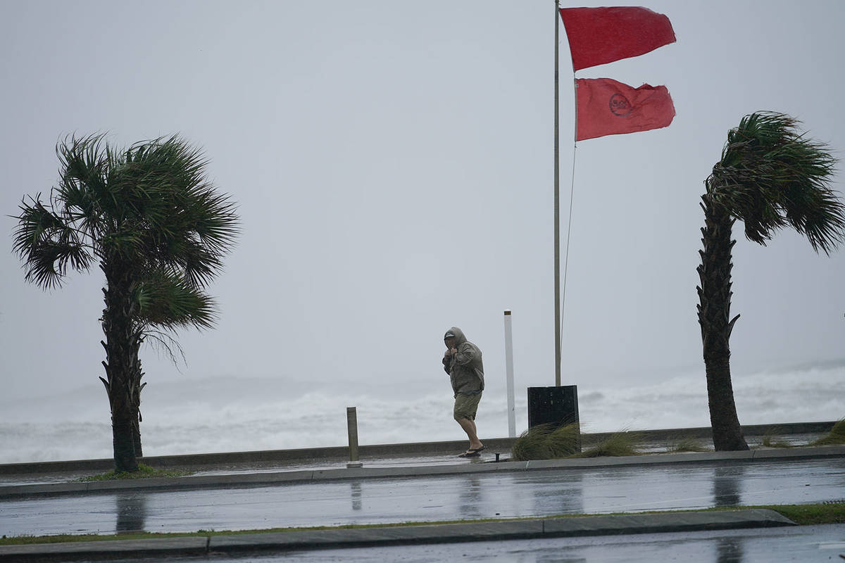 A man walks bear the gulf as Hurricane Sally moves in, Tuesday, Sept. 15, 2020, in Gulf Shores, ...