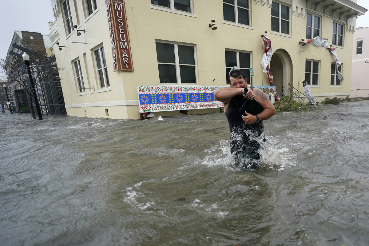 Trent Airhart wades through flood waters, Wednesday, Sept. 16, 2020, in downtown Pensacola, Fla ...