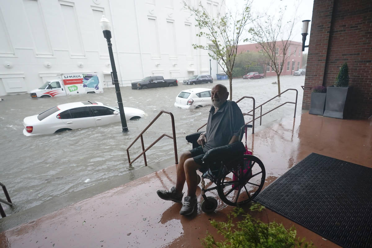 A man watches flood waters, Wednesday, Sept. 16, 2020, in downtown Pensacola, Fla. Hurricane Sa ...