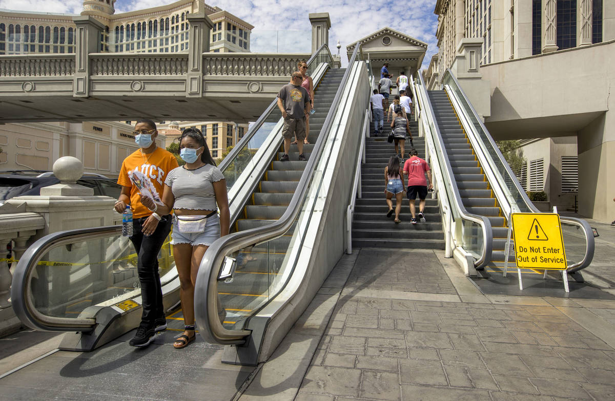 Pedestrians work their way down and up the bridge that crosses East Flamingo Road between Caesa ...