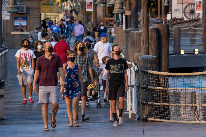 Visitors wander about Treasure Island along the Strip on Friday, August 7, 2020, in Las Vegas. ...