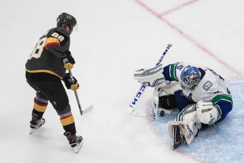 Vancouver Canucks goalie Thatcher Demko (35) makes a save on Vegas Golden Knights' Nate Schmidt ...