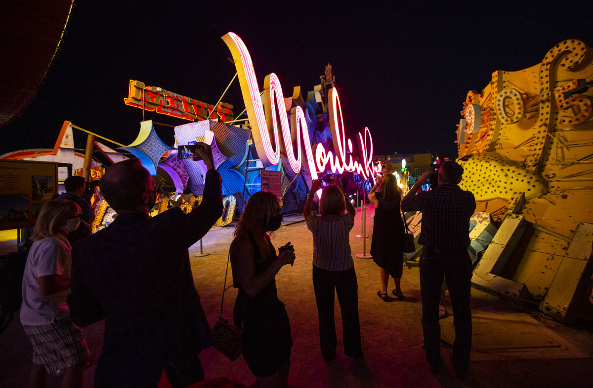 People take photos as the Moulin Rouge sign is reilluminated at the Neon Museum in Las Vegas on ...