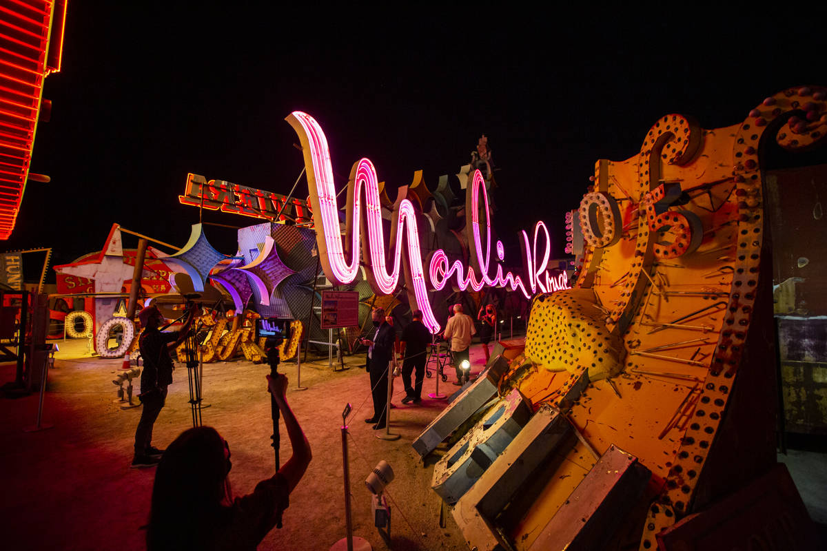 People take photos and record video as the Moulin Rouge sign is reilluminated at the Neon Museu ...