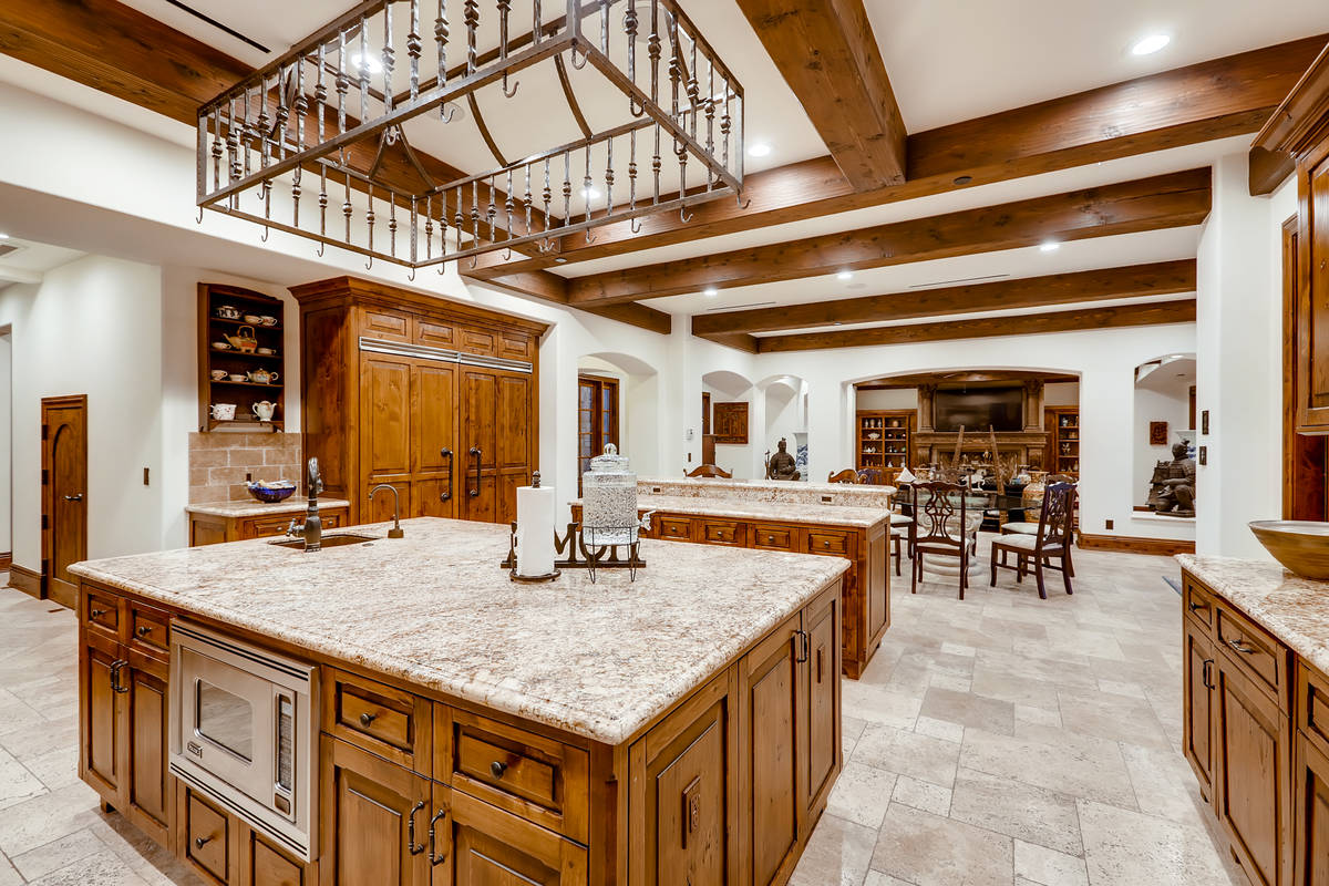 The kitchen has upgraded appliances and a large central island with seating. It leads to the la ...