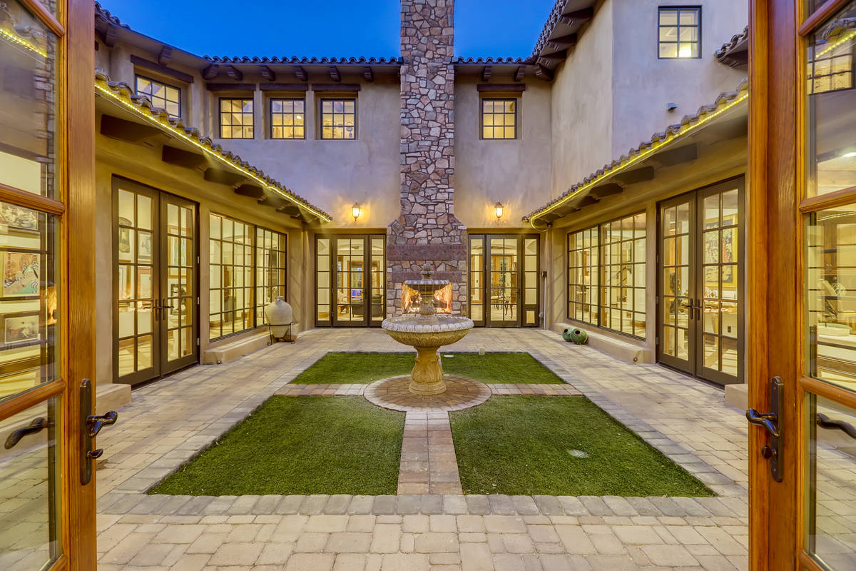 A large square interior courtyard greets visitors as they enter the home. It's park-like settin ...