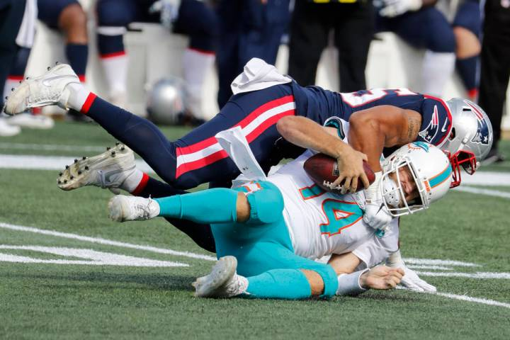 Miami Dolphins quarterback Ryan Fitzpatrick is sacked by New England Patriots defensive end Der ...