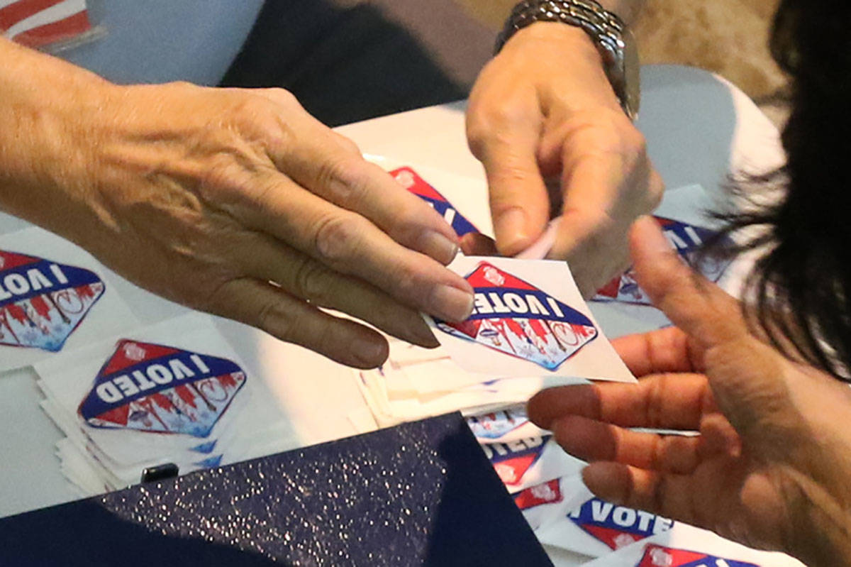 """A worker hands out """"I Voted """" sticker to a voter at a polling station at Galleria Mall on Tuesd ..."""
