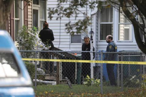 Rochester police look over the area of a home after a fatal shooting at a backyard house party, ...