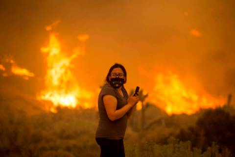 A woman watches as the Bobcat Fire burns in Juniper Hill, Calif., Friday, Sept. 18, 2020. (AP P ...