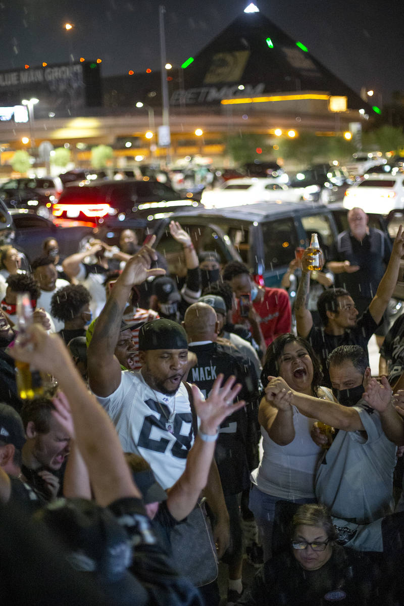 Raiders fans celebrate a Raider touchdown outside Allegiant Stadium on Monday, Sept. 21, 2020, ...