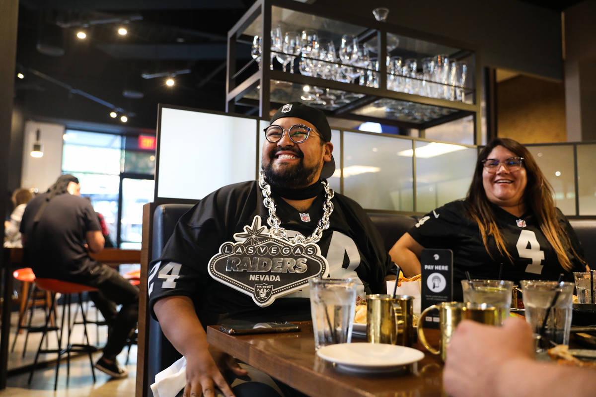 Mike Aguiniga, left, watches the Raiders first home game next to his wife Madi Aguiniga, right, ...