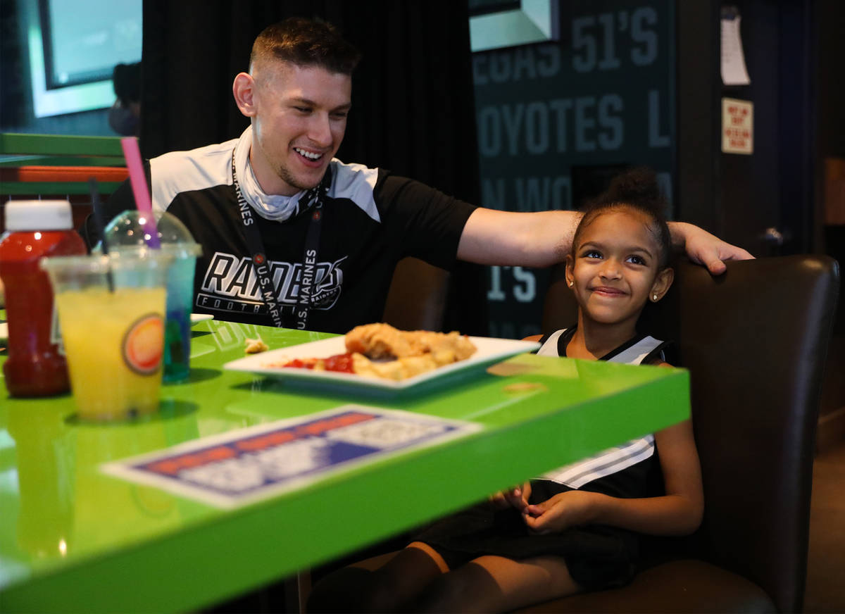 John Woodward watches the Raiders first home game with his daughter Zoe Woodward, 5, at Dave an ...