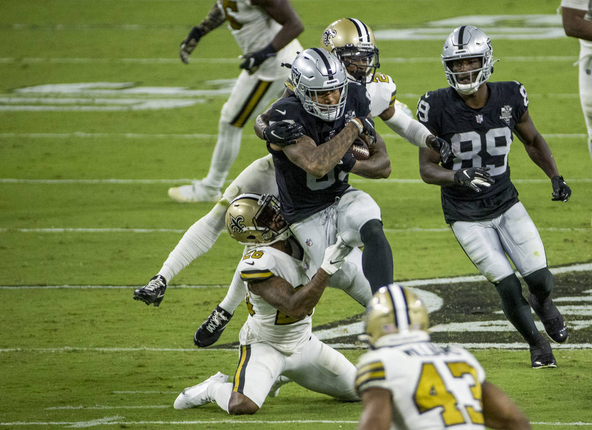 Las Vegas Raiders tight end Darren Waller (83) battles through a tackle attempt by New Orleans ...
