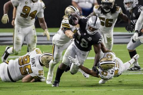 Las Vegas Raiders running back Josh Jacobs (28) breaks free from New Orleans Saints defensive e ...