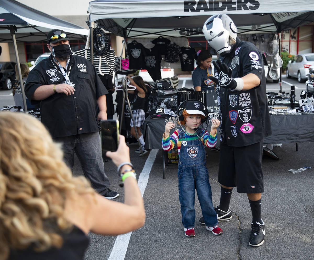 Julian Segura, 5, of Los Angeles, poses with Raider Iron Man, of Arizona, at a Raiders party at ...