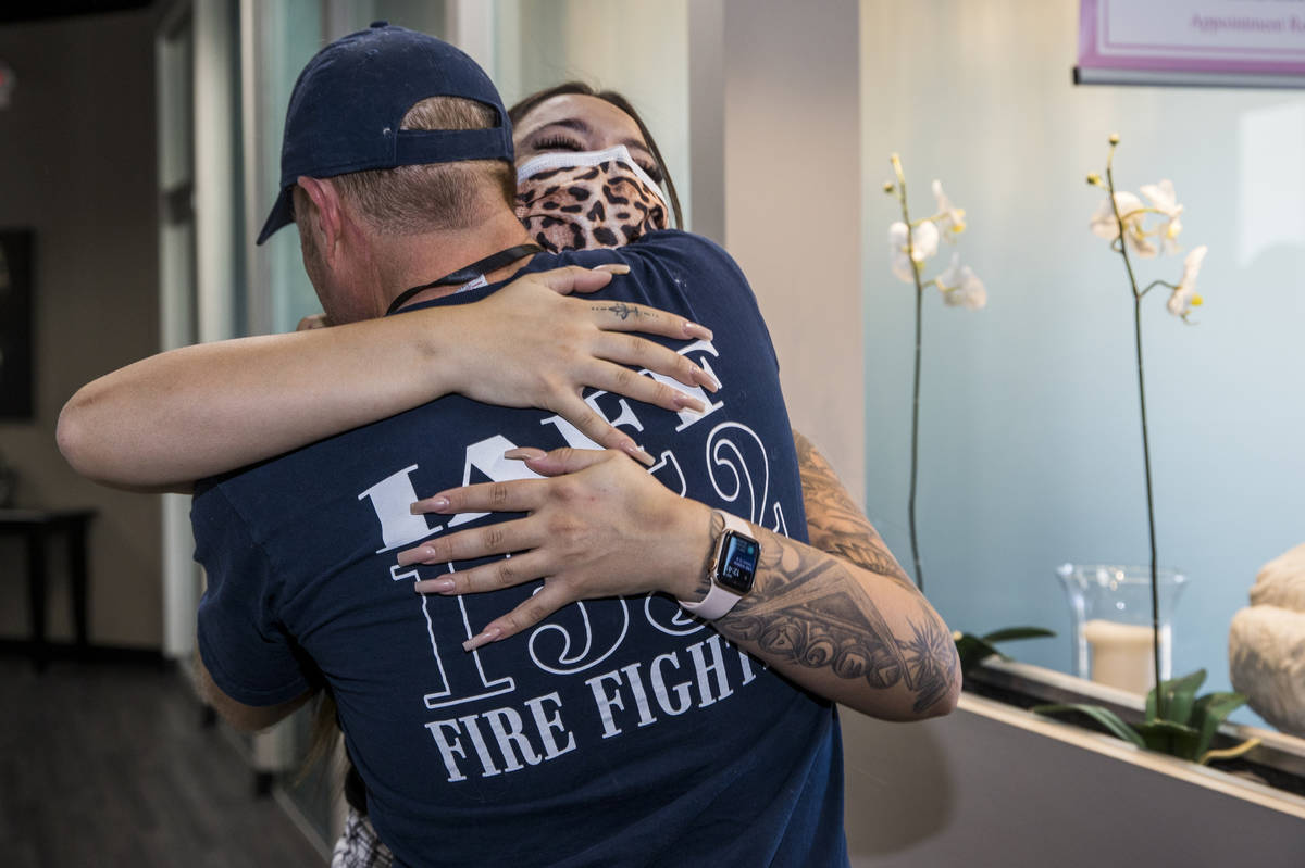 Seattle firefighter Dean McAuley, back, greets Natalia Baca whom he saved after a gunshot wound ...