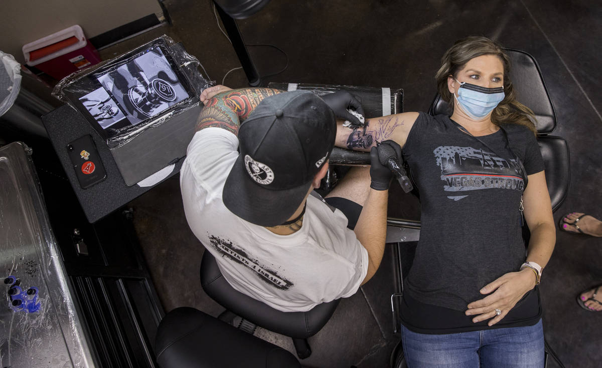 Tattoo artist Jeremy Hill, left, works on Rhonda Davis as Route 91 shooting survivors and first ...