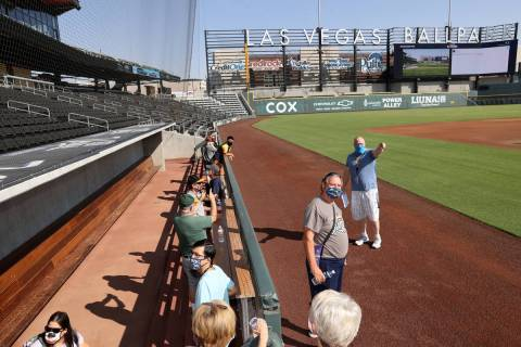 Gary Arlitz, director of game entertainment, gives a tour as fans check out the visitor dugout ...
