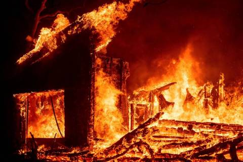 Flames from the Glass Fire consume a vineyard building in St. Helena, Calif., on Sunday, Sept. ...