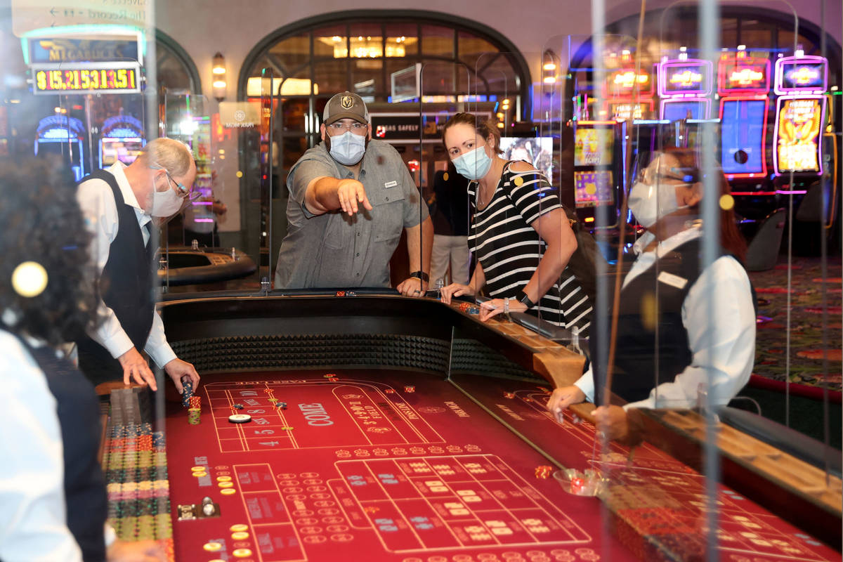 Matt and Angela Tooley of Temple, Texas play craps as Park MGM reopens after the coronavirus sh ...