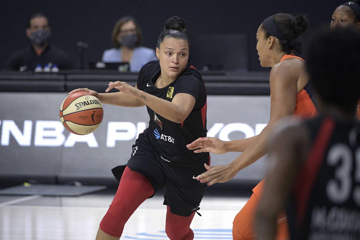 Las Vegas Aces guard Kayla McBride, left, drives to the basket in front of Connecticut Sun cent ...