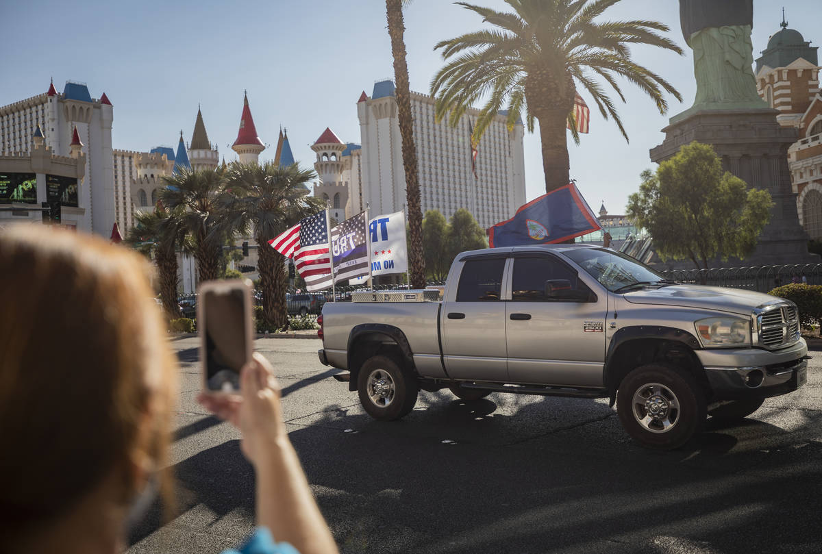 Individuals cheer as a caravan of Trump supporters ride down the Las Vegas Strip on Wednesday, ...