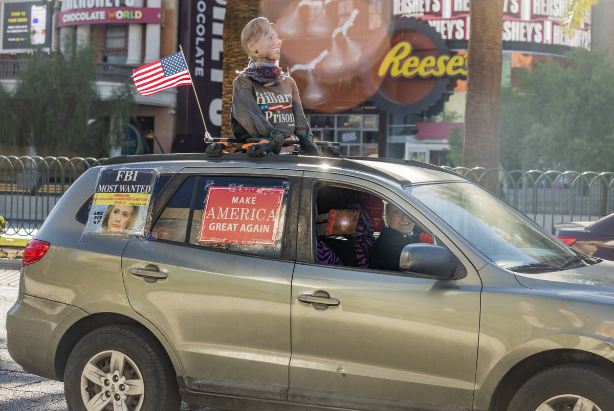 A car taking part in a caravan of Trump supporters, rides down the Las Vegas Strip, on Wednesda ...