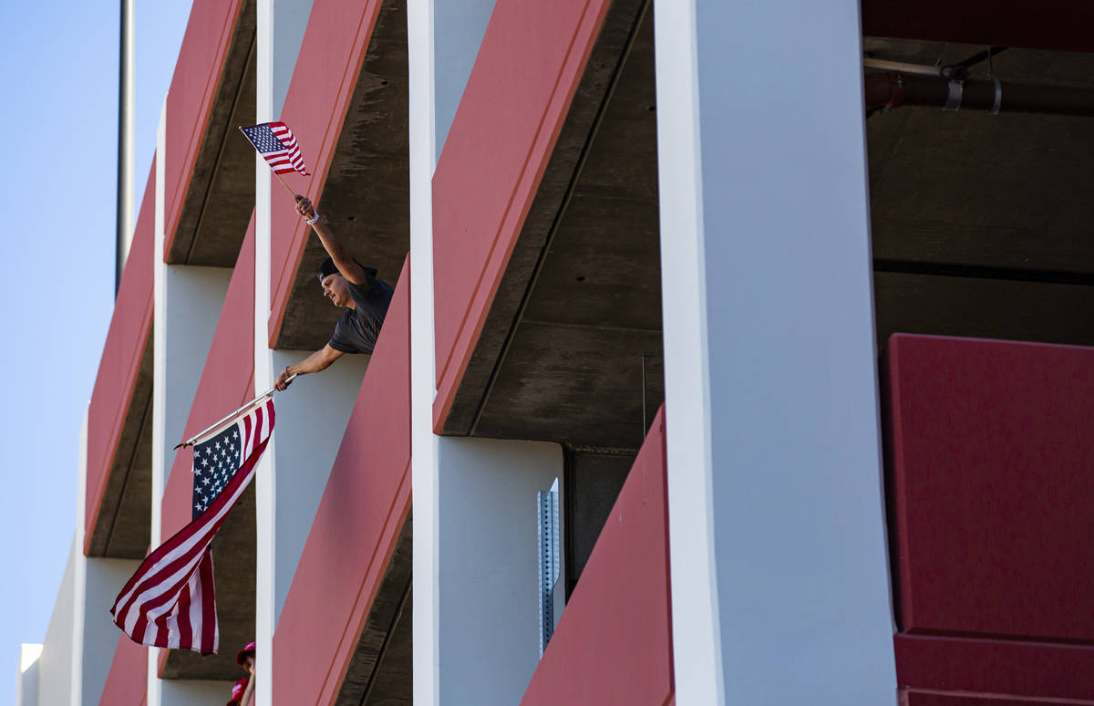 A man waves flags from the parking garage of the Ahern Hotel as supporters of law enforcement a ...